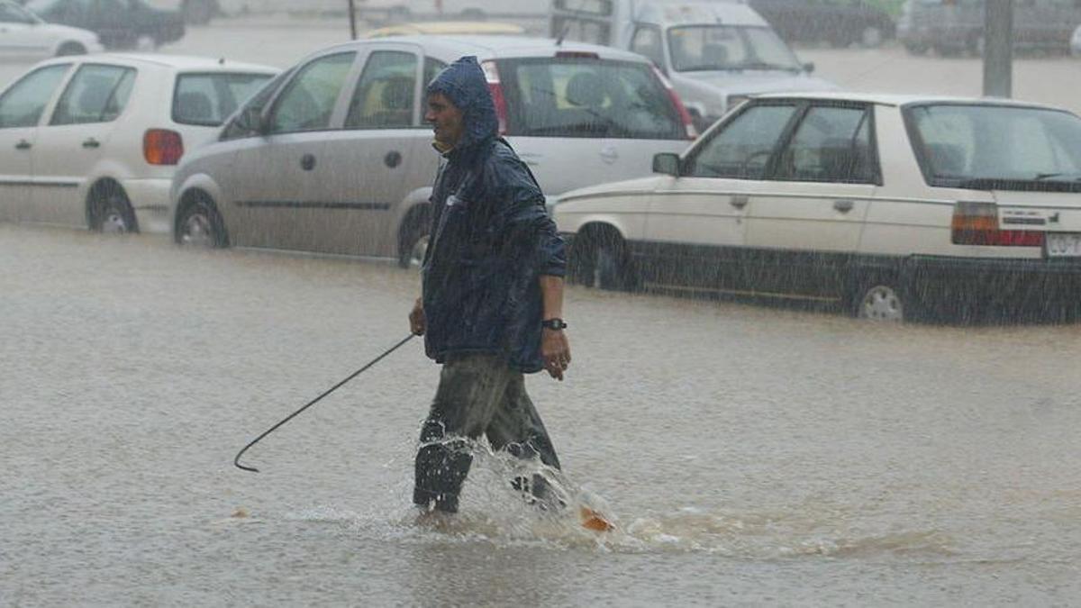 Un hombre camina por una calle inundada de Córdoba durante las lluvias provocadas por Vince en 2005 / Madero Cubero.