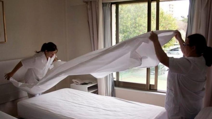 Dos empleadas realizan tareas de acondicionamiento de una habitación hotelera