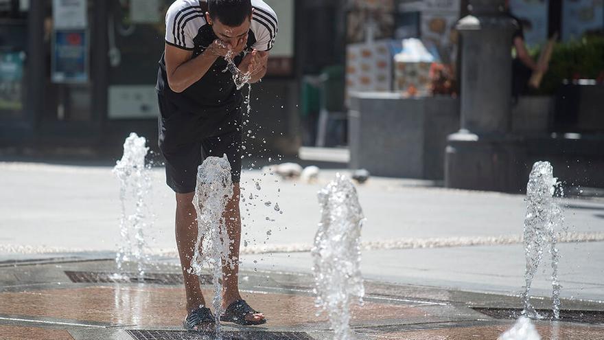 Un joven se refresca en Las Tendillas | TONI BLANCO