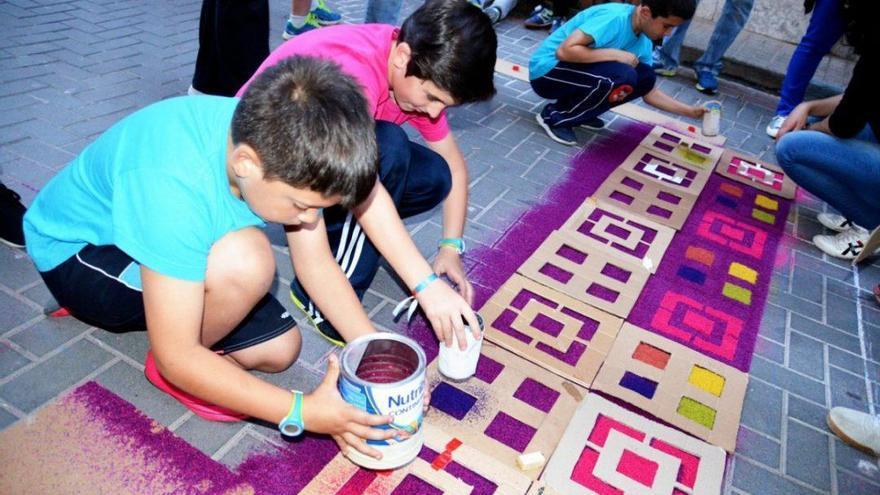 Niños trabajando en una alfombra de serrín en Elche de la Sierra