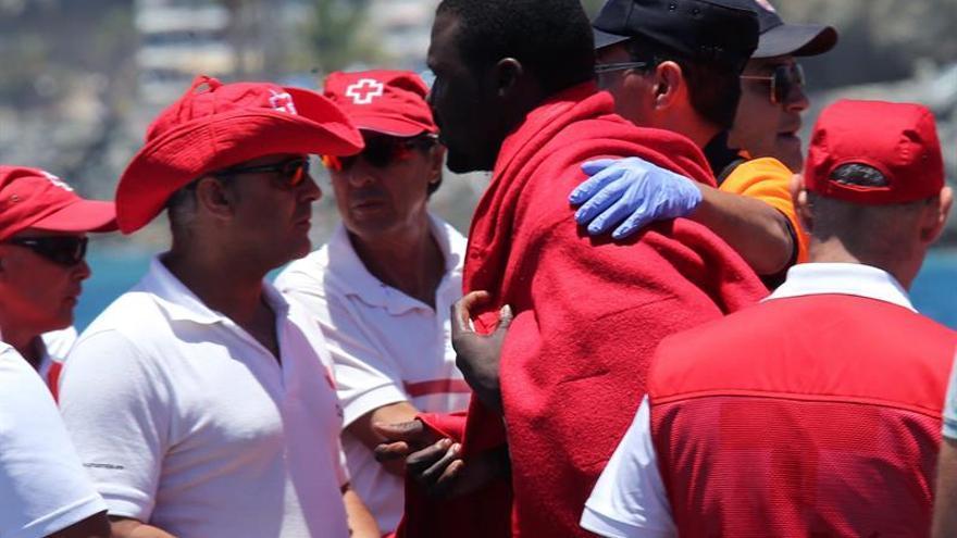 Un voluntario de Cruz Roja atiende en el muelle de Arguineguín (Mogán) a algunos de los 58 inmigrantes que Salvamento Marítimo rescató en aguas cercanas al sur de Gran Canaria. EFE/Elvira Urquijo A.