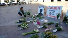 Una mujer dejando su ofrenda floral por los desaparecidos en Zaldibar en la plaza de Eibar