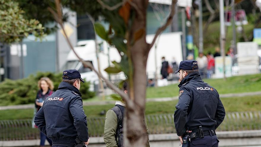 Dos agentes de la Policía Nacional abordan a un ciudadano durante el estado de alarma