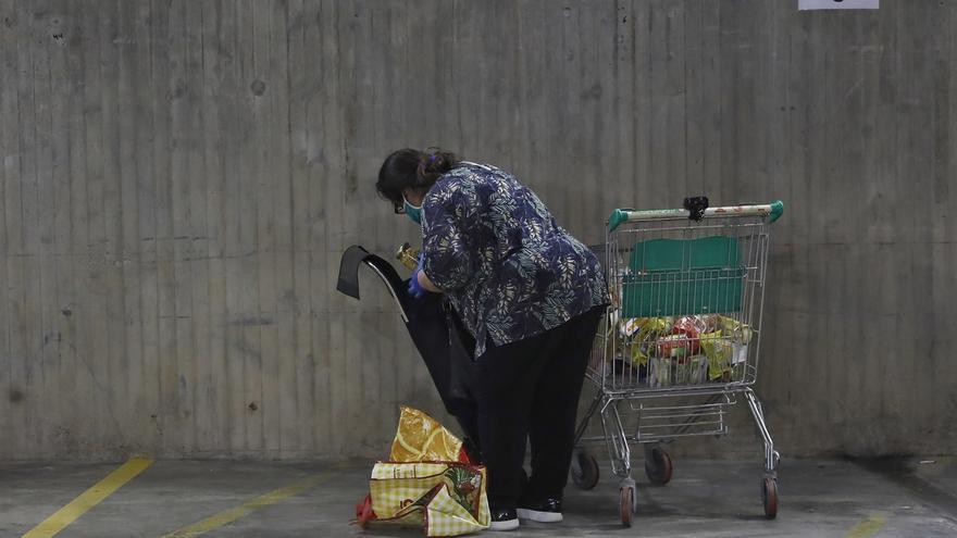 Una ciudadana recoge comida en un banco de alimentos para familias vulnerables.
