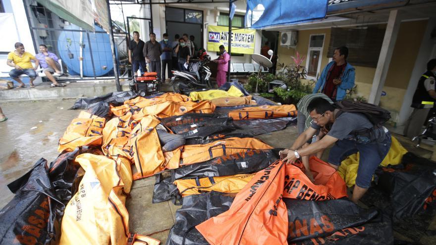 La gente busca a sus parientes entre los cuerpos de las víctimas del tsunami en Carita, Indonesia