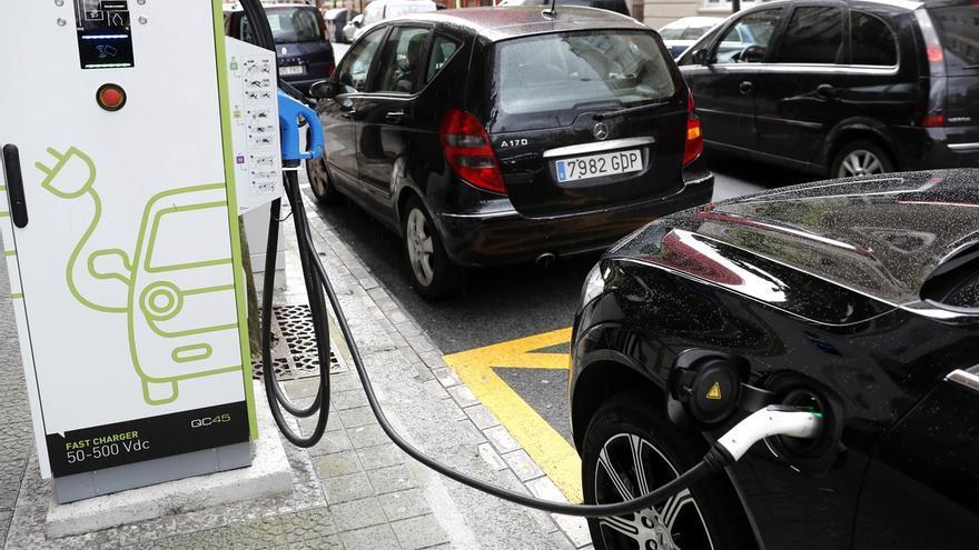 Un coche híbrido y eléctrico, se recarga de una electrolinera.