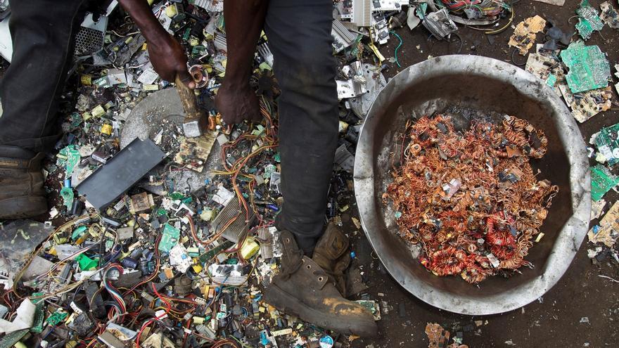 Un hombre rescata hilos de cobre de entre restos de aparatos tecnológicos en un vertedero.