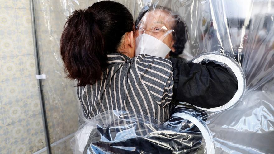 """Patricia Camargo (i) fue registrada este jueves al abrazar a su madre, Maria Helena -de 75 años-, a través de una """"cortina de abrazos"""", una alternativa válida para amenizar las medidas de distanciamiento social, durante el avance de la pandemia del coronavirus, en un ancianato de la ciudad de Sao Paulo (Brasil)."""