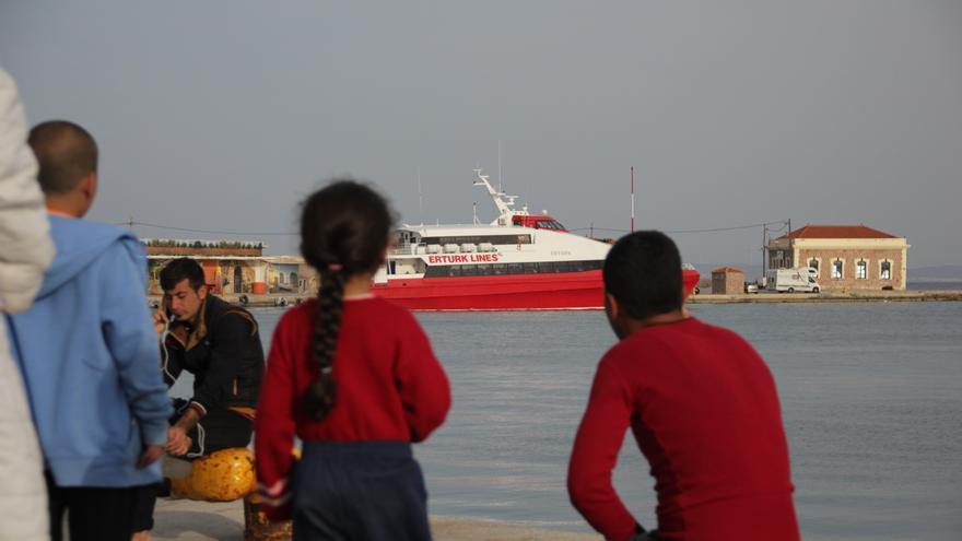 Varios niños refugiados observan el ferri en el que horas antes han sido deportados a Turquía 66 refugiados y migrantes desde la isla de Quíos. | Daniel Rivas Pacheco