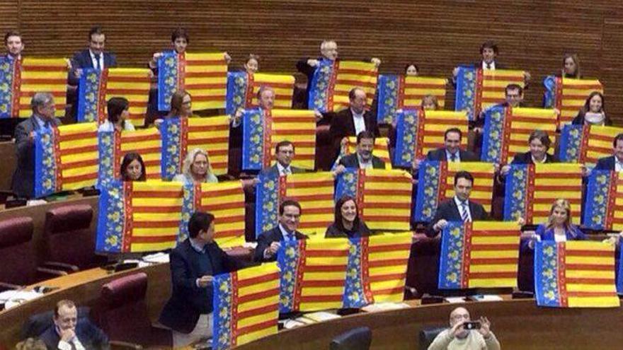 Los diputados del PP con senyeres en sus escaños de las Corts Valencianes tras la derogación de la Ley de Señas de Identidad.