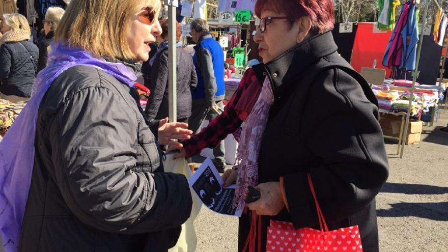 Una mujer informando a otra sobre la huelga feminista en el mercadillo de La Elipa
