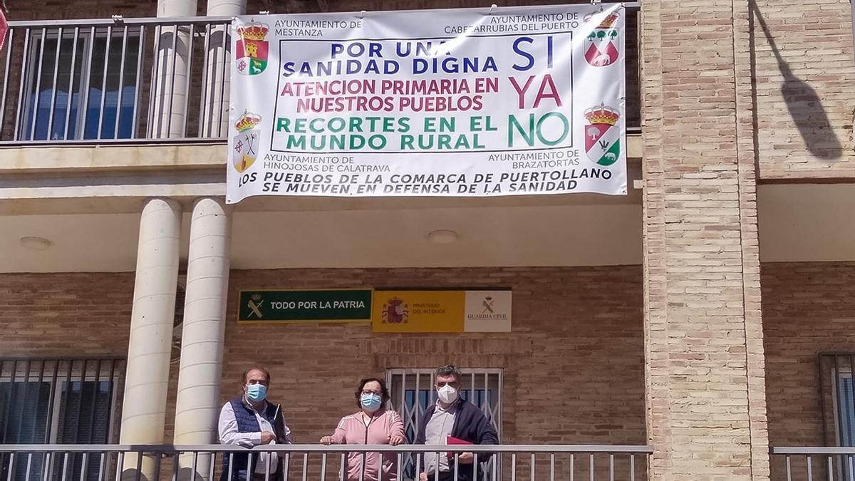 Desde la izquierda, los alcaldes de Cabezarrubias, Hinojosas y Mestanza, bajo la pancarta reivindicativa en el consistorio mestanceño.jpg