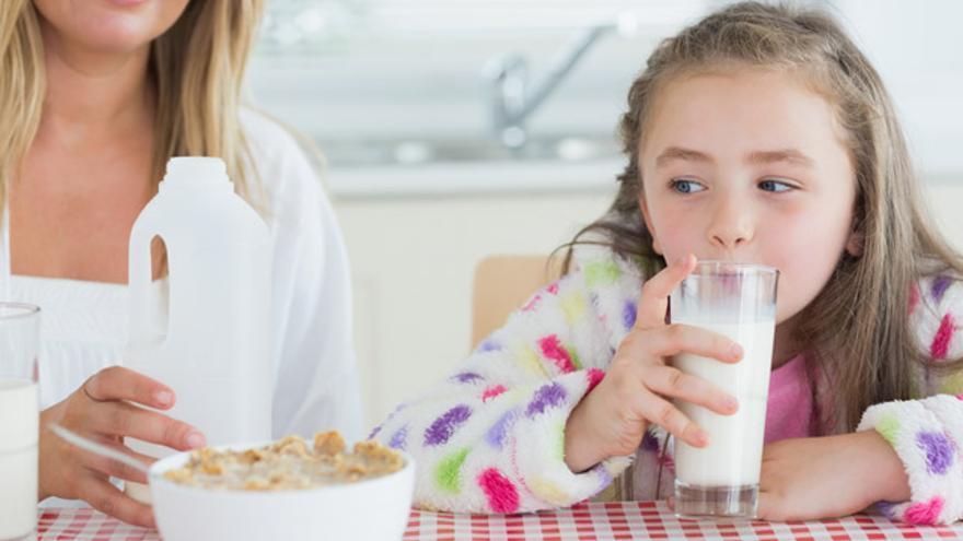 Una niña bebiendo leche.