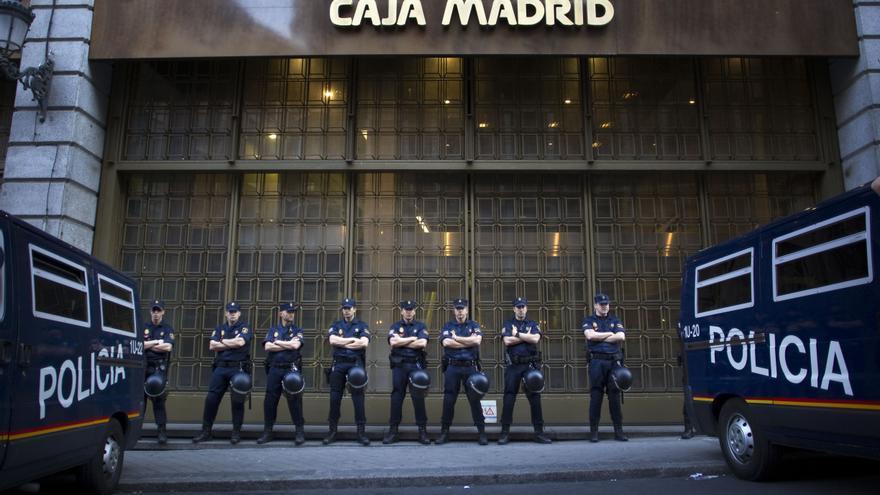 Policías vigilan una sede de Caja Madrid, en mayo de 2012.