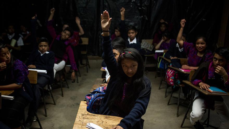 Varios alumnos levantan sus manos al ser preguntados sobre la situación migratoria de sus familiares