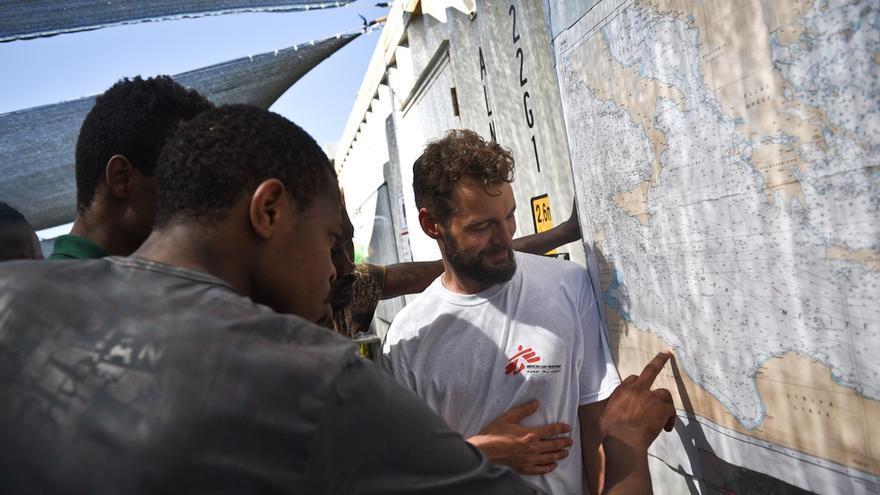 Refugiados miran un mapa de Italia en la cubierta del Bourbon Argos // Copyright: Sara Creta/MSF
