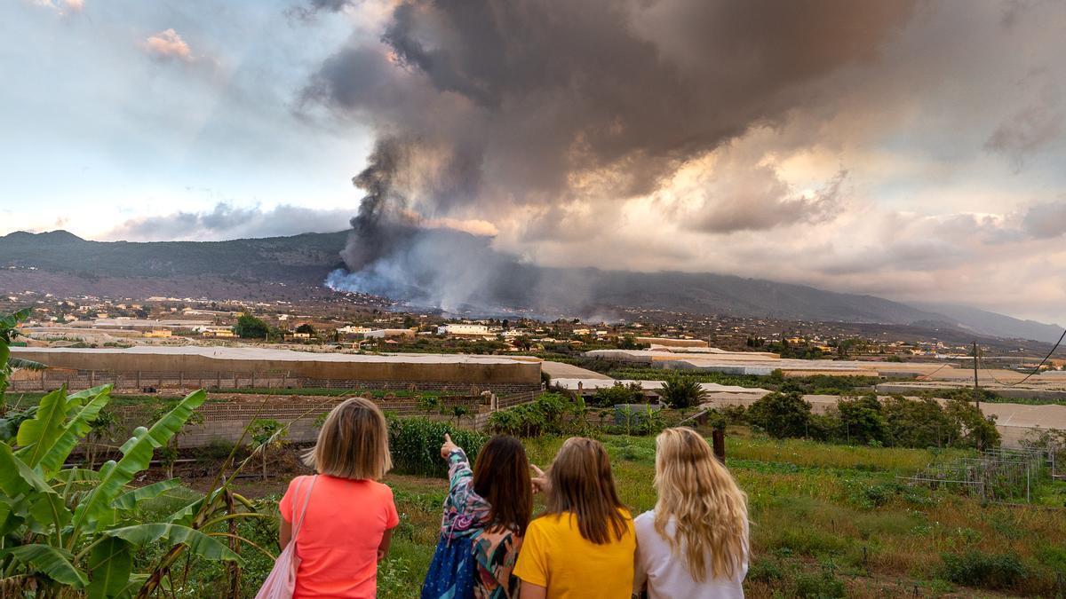 Un grupo de personas frente a terrenos de cultivos y al fondo el avance de la lava del volcán en La Palma.