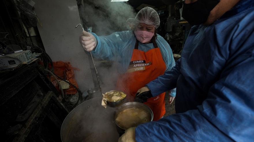 Vecinos preparan almuerzos el 30 de junio de 2020 durante una olla común, destinada a ayudar a las familias vulnerables y a las personas sin techo del sector afectadas por la pandemia de COVID-19, en la comuna de Conchalí, en Santiago (Chile).
