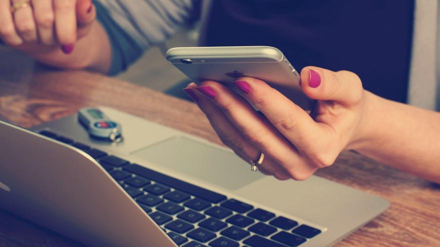 Una mujer usa una app de reciclaje en su móvil.