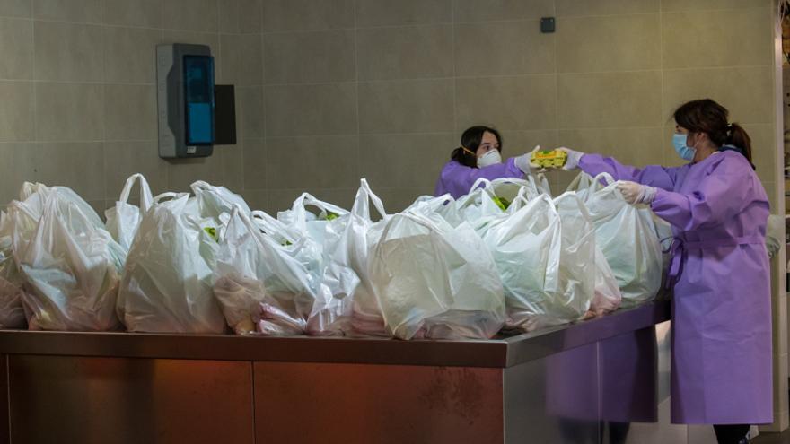 Dos trabajadoras meten productos frescos en las bolsas para distribuirlo.
