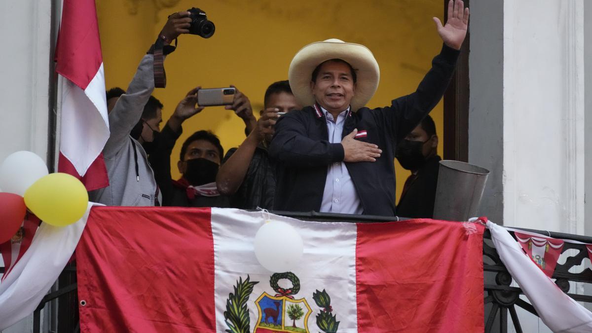 Pedro Castillo saluda a los partidarios que celebran los resultados parciales de las elecciones en la sede de su campaña en Lima, el día después de una segunda vuelta presidencial.