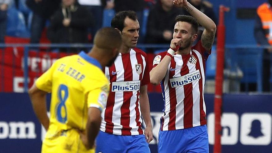 El centrocampista del Atlético de Madrid Saúl Ñíguez (d) celebra junto a su compañero, el defensa argentino Diego Godín (i), el primer gol del equipo frente a Las Palmas, durante el partido de la decimosexta jornada de la Liga de Primera División en el Vicente Calderón, en Madrid. EFE/Ballesteros