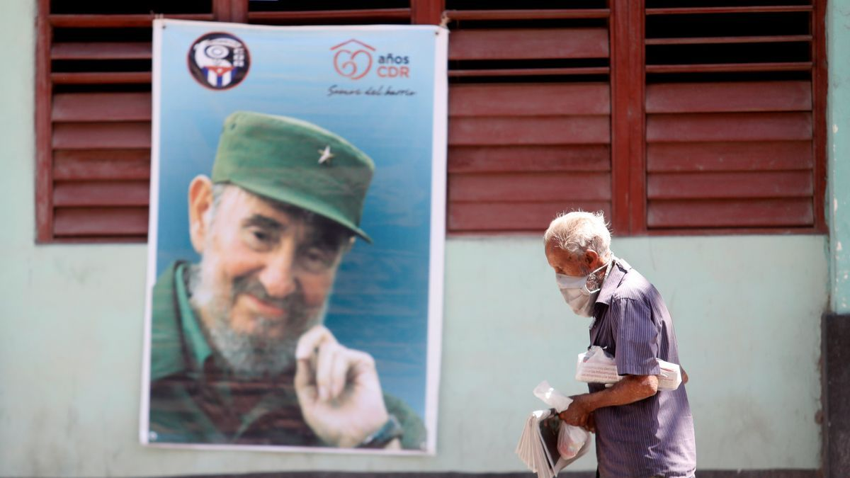 Un hombre con mascarilla camina frente a una imagen de Fidel Castro en una calle de La Habana (Cuba). EFE/ Yander Zamora/Archivo