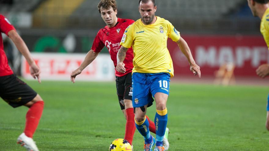 El jugador de la UD Las Palmas Apoño conduce el balón ante la mirada de varios jugadores del CD Mirandés. udlaspalmas.es