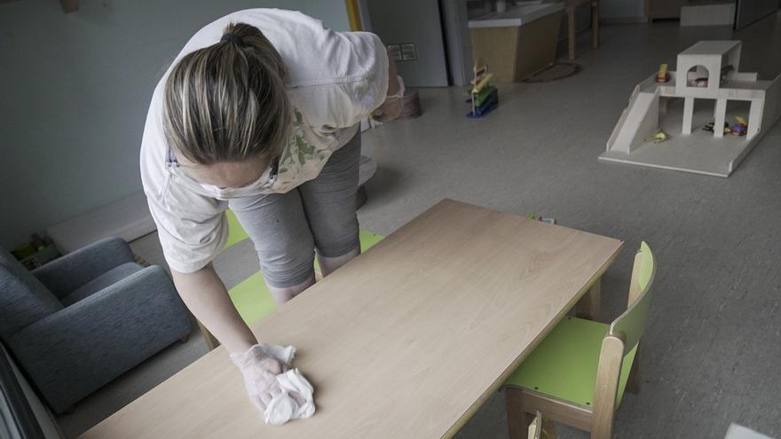 Una educadora desinfecta el mobiliario y materiales usados en la escuela infantil La Llum