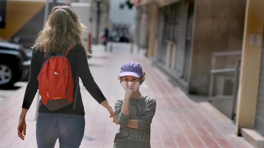 Un niño con mascarilla hace la señal de la victoria mientras pasea por la calle en València en el primer día de desconfinamiento para menores de 14 años.