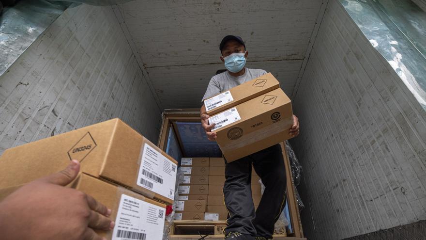 Trabajadores de Katmandú descargan cajas que contienen la vacuna de Janssen contra la COVID-19.