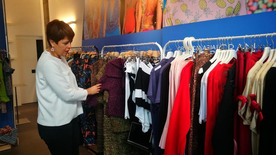 La consejera insular Minerva Alonso mira algunos de los diseños que se venderán rebajados en la sede de la Fedac del barrio capitalino de Triana.
