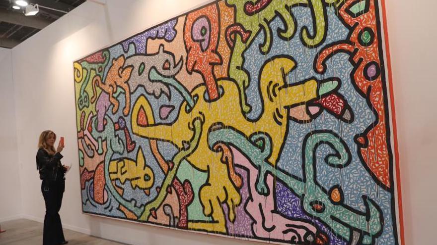 Una mujer observa una obra del artista estadounidense Keith Haring .