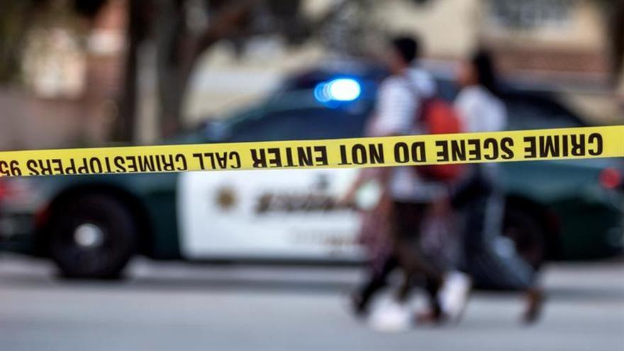 Un grupo de personas camina frente a la zona acordonada tras el tiroteo de Parkland.