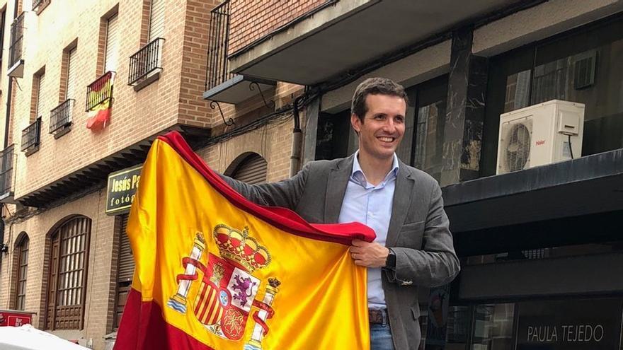 Pablo Casado posa con la bandera de España sobre el capó de un coche.