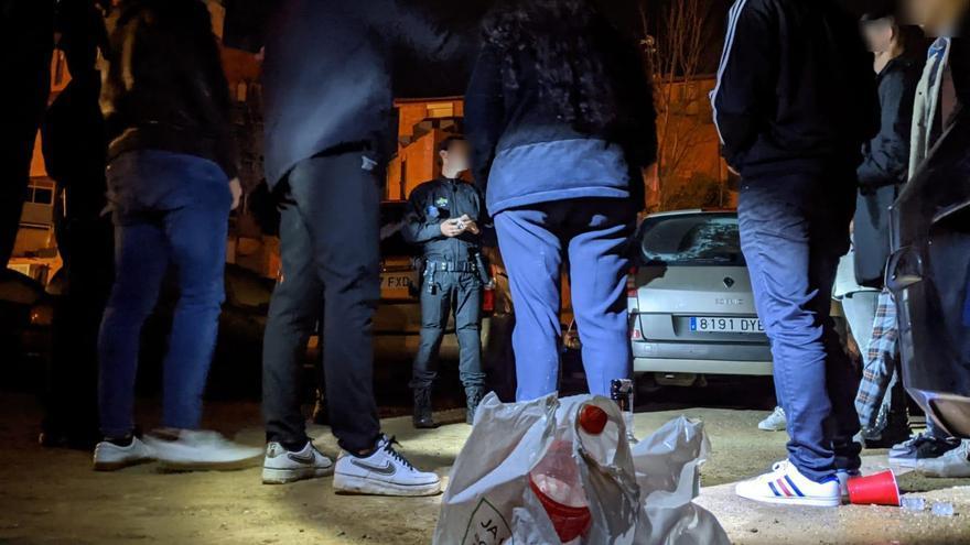 Agentes de la Policía Municipal junto a unos jóvenes haciendo botellón en Reus (Tarragona).