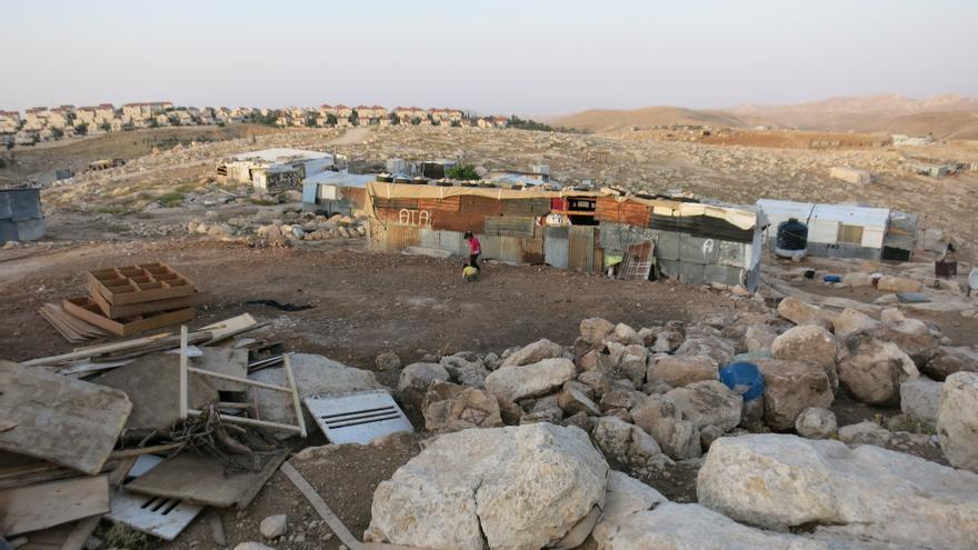 Detrás de los restos de una caseta destrozada y otras que aún permanecen levantadas se vislumbran los tejados rojos de la colonia más grande de las afueras de Jerusalén, Maale Adumim/ Ana Garralda