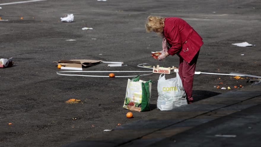 Un mujer recogiendo comida de Mercamadrid en 2012, en una foto de archivo / OLMO CALVO