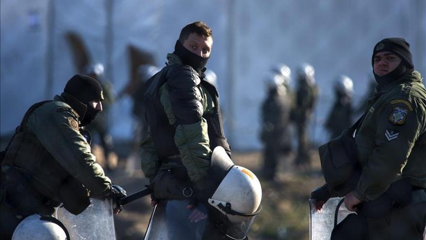 Fotografía tomada desde el lado macedonio de la frontera que muestra a un grupo policías griegos en un campamento cerca de Idomeni, en Grecia, este enero.