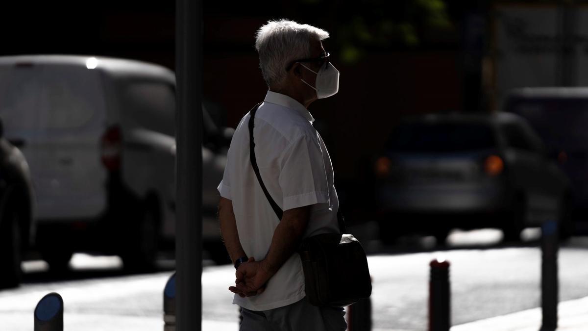 Un hombre camina por una calle de Santa Cruz de Tenerife haciendo uso de mascarillas para prevenir el contagio del COVID-19.