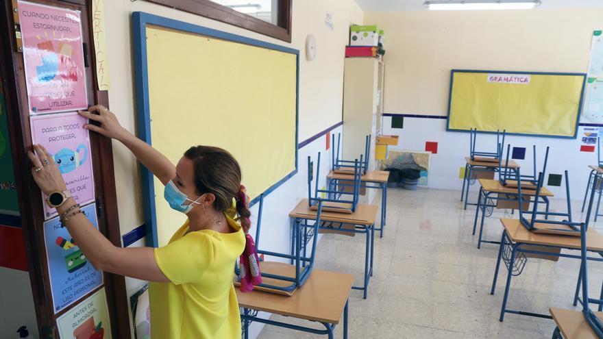 Una profesora coloca carteles de medidas preventivas ante el COVID-19 en un aula. Archivo