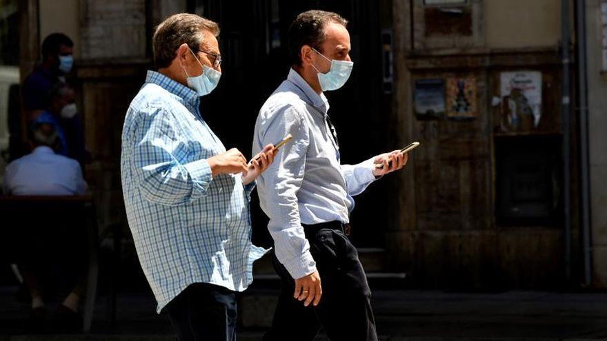 Dos hombres con mascarilla y móviles en mano pasean por una calle de Almería