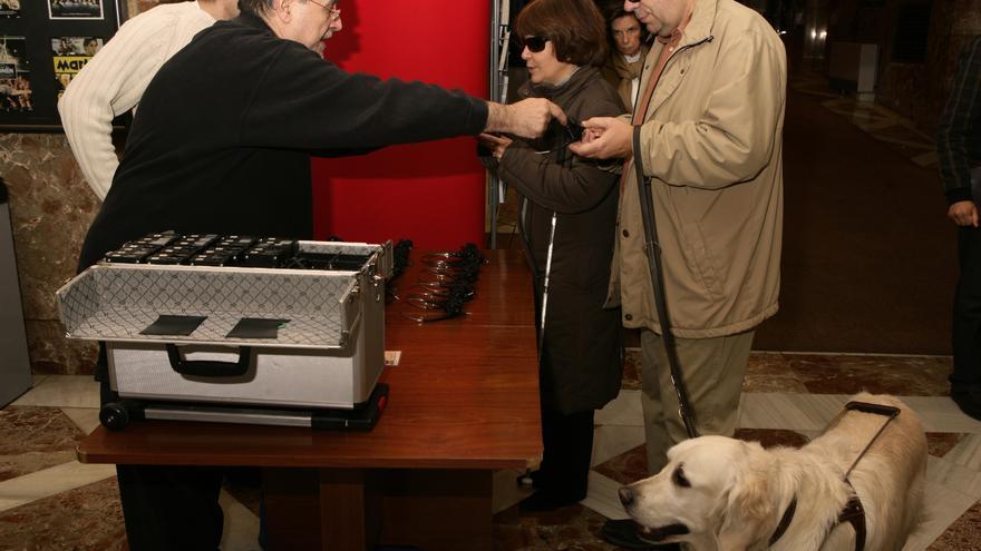 Personas invidentes recogen las petacas de transmisión por radio antes de que comience la sesión (Foto: ONCE)