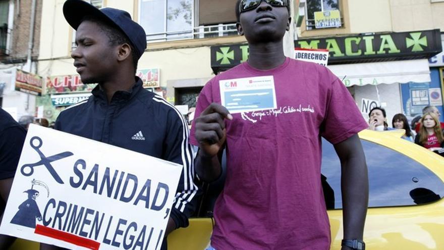 Dos personas protestan contra la exclusión sanitaria y los recortes