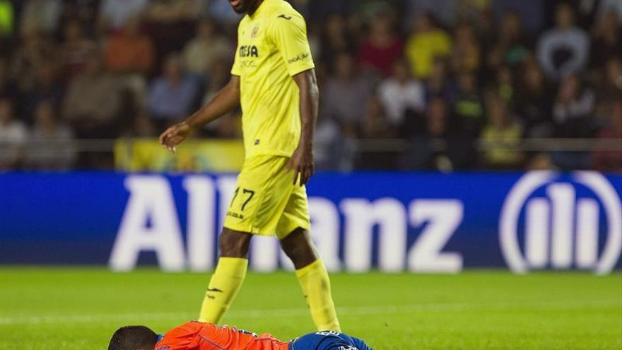 El delantero francés del Villarreal Bakambu observa al brasileño de la UD Las Palmas Michel (en el suelo), que se retiró lesionado, durante el partido de la novena jornada de Liga en Primera División disputado en el estadio de El Madrigal, en Villarreal. EFE/Miguel Ángel Polo