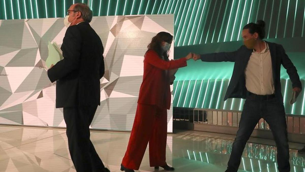 Monica García choca el puño con Pablo Iglesias mientras Ángel Gabilondo cruza en el plató del debate.