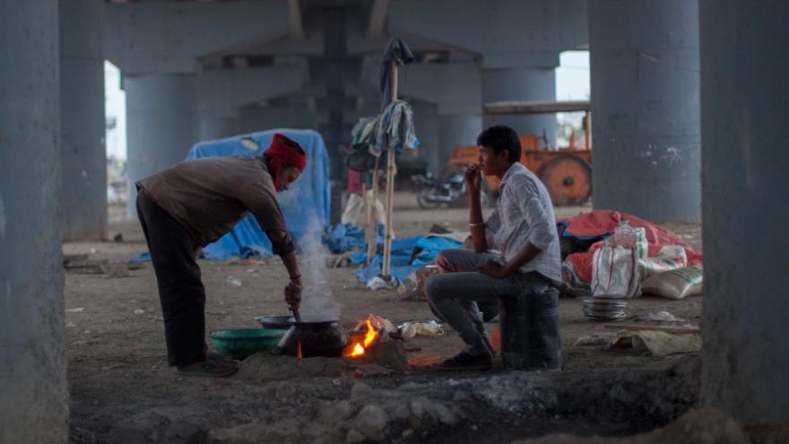 Dos habitantes del slum de Chola cocinan bajo uno de los puentes de la autopista. // FOTO: Bernat Parera