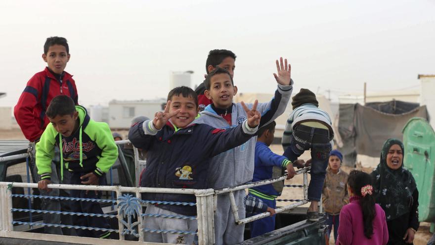 Niños refugiados sirios saludan ante el paso de un convoy de ACNUR en el campo de refugiados de Zattari, en Jordania