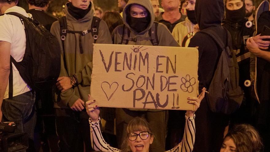 """Una manifestante durante las movilizaciones de este sábado sostiene un cartel en el que puede leerse """"venimos en son de paz"""""""