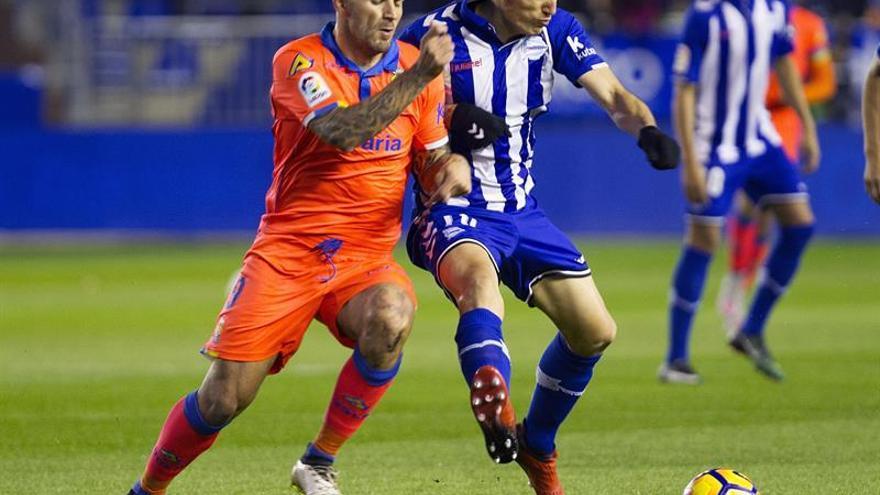 El jugador del Deportivo Alavés Edgar Méndez (d) pelea un balón con el croata Marko Livala, de la UD Las Palmas, durante el partido de Liga en Primera División disputado en el estadio de Mendizorrotza, en Vitoria. EFE/Adrián Ruiz de Hierro